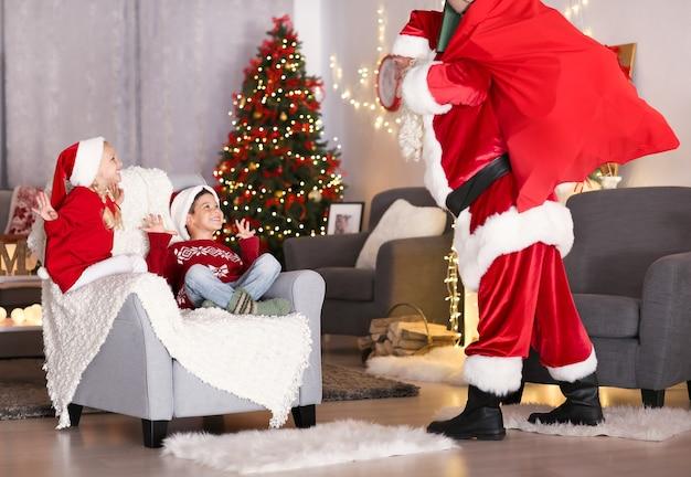 Süße kinder freuen sich, den weihnachtsmann mit großer geschenktüte im weihnachtlich dekorierten zimmer zu sehen