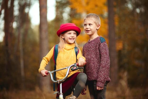 Süße kinder in bunten kleidern, bruder und schwester, gehen mit dem fahrrad im herbstpark spazieren und unterhalten sich