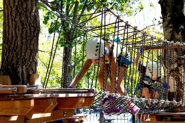 Süße kinder. jungen und mädchen, die in einer seilspielplatzstruktur am abenteuerpark klettern.