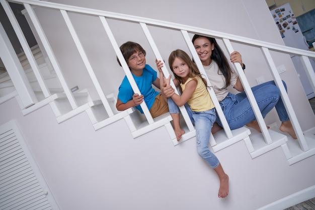 Süße kinder, kleine jungen und mädchen, die zeit mit ihrer jungen positiven mutter verbringen, während sie zusammen sitzen