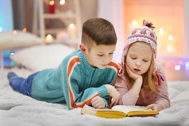Süße kinder lesen ein buch auf dem boden im dekorierten zimmer