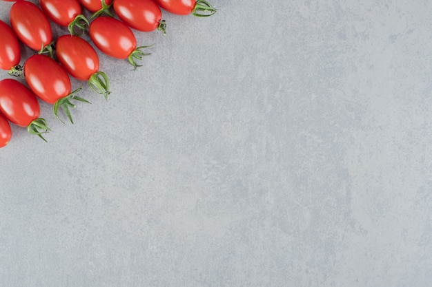 Süße kirschtomaten isoliert auf betonoberfläche