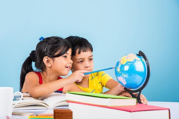 Süße kleine indische oder asiatische kinder, die auf einem studientisch mit bücherstapel, bildungsglobus, isoliert über hellblauer farbe