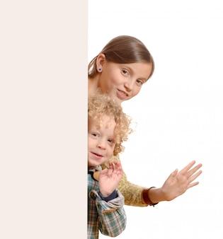 Süße kleine kinder hinter einem weißen brett
