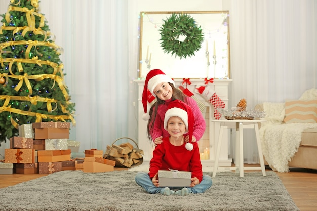 Süße kleine kinder in weihnachtsmützen mit weihnachtsgeschenk zu hause