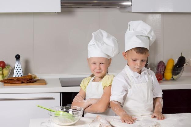 Süße kleine köche, die in der küche etwas zu essen machen.