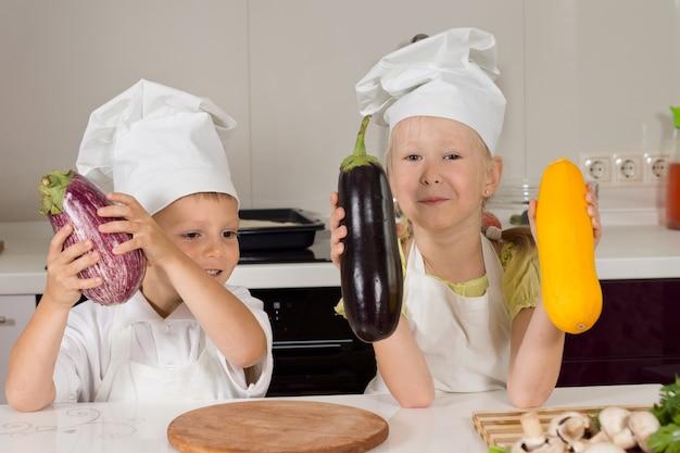 Süße kleine köche, die riesiges gemüse in der küche zeigen.