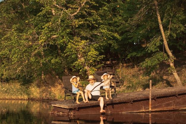 Süße kleine mädchen und ihr opa fischen am see oder fluss