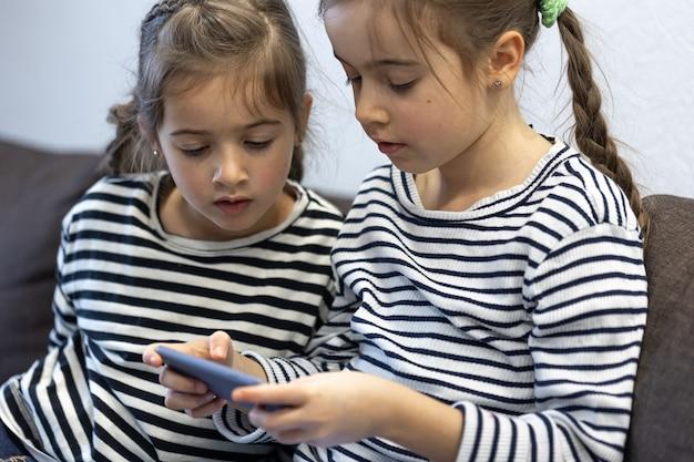 Süße kleine schwestern benutzen telefone, während sie zu hause auf der couch sitzen.