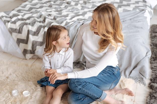 Süße kleine tochter und ihre schöne mutter sitzen auf dem teppich und schauen sich mit einem lächeln an, während die mutter etwas creme auf ihre hand aufträgt