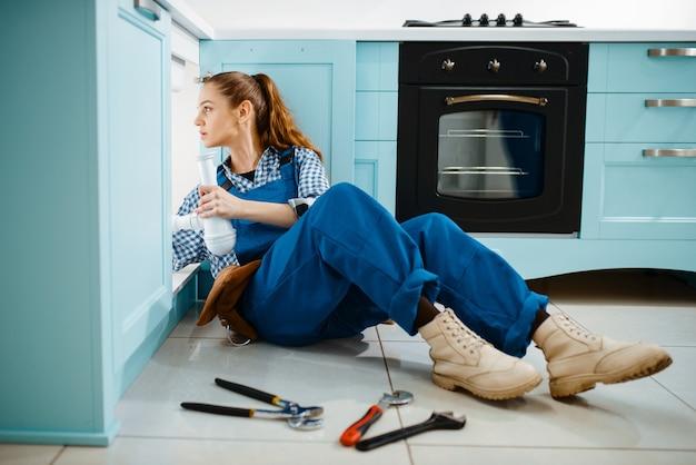 Süße klempnerin in uniform hält abflussrohr in der küche. heimwerkerin mit werkzeugtaschen-reparaturspüle, sanitäranlagen-service zu hause