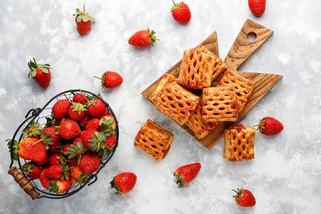 Süße köstliche erdbeerplätzchen mit reifen erdbeeren, draufsicht
