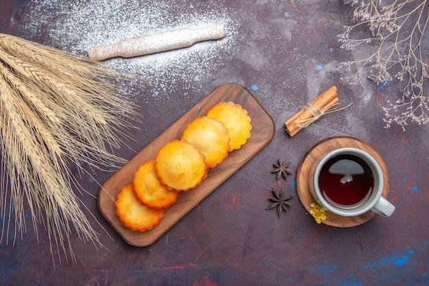 Süße kuchen von oben mit einer tasse tee auf dunkler oberfläche kuchenkuchen keks süßer keks tee