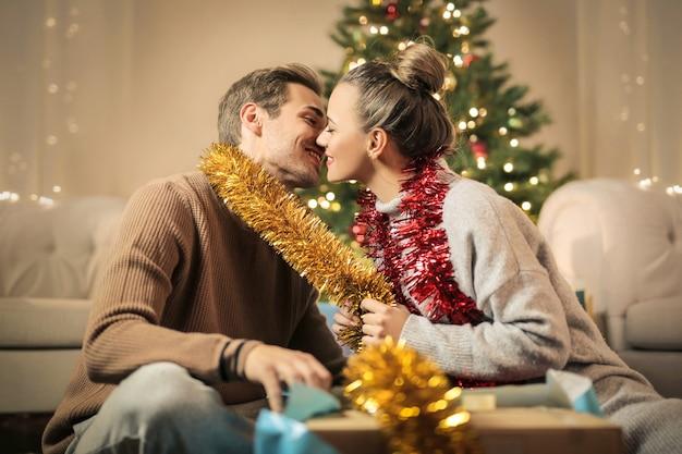 Süße küssende paare, während weihnachtsdekorationen vorbereitet werden