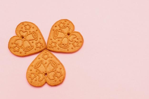 Süße lebkuchenplätzchen, die eine herzform auf rosa hintergrund mit kopienraum-valentinstag-lebensmittelkonzept bilden.