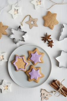 Süße lebkuchenplätzchen glasiert mit violettem zuckerguss, serviert auf grauem teller auf tisch mit girlande