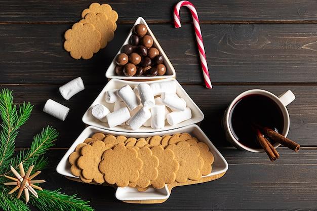 Süße leckereien auf einem weihnachtsbaumförmigen schnittteller
