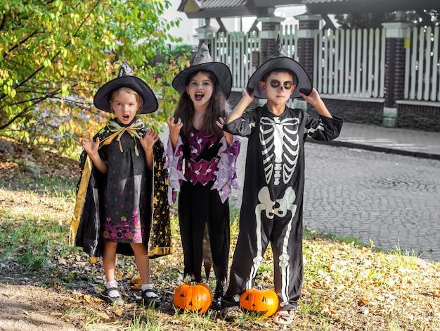 Süße lustige kinder in halloween-kostümen von hexen und skelett