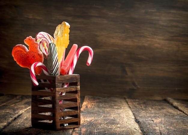 Süße lutscher in einem holzständer. auf einem hölzernen hintergrund.
