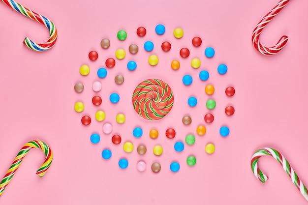 Süße lutscher und zuckerstangen auf rosa hintergrund, kopienraum. liebe zu bunten süßigkeiten im kindheitskonzept