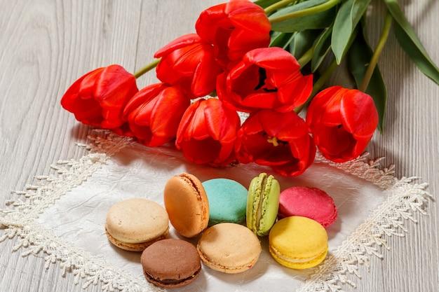Süße macarons kuchen in verschiedenen farben auf seidenserviette mit strauß frischer roter tulpen mit holzhintergrund