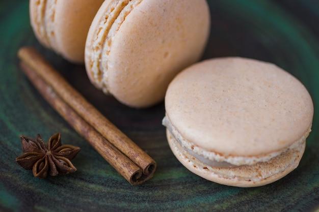 Süße macarons und anisstern auf einem grünen tisch. nahansicht