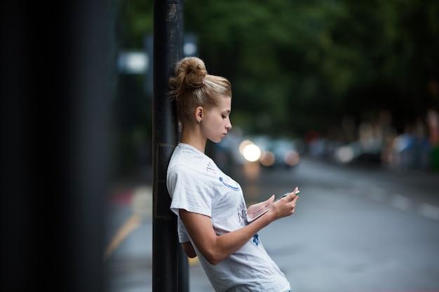 Süße mädchen mit tablet an einer bushaltestelle
