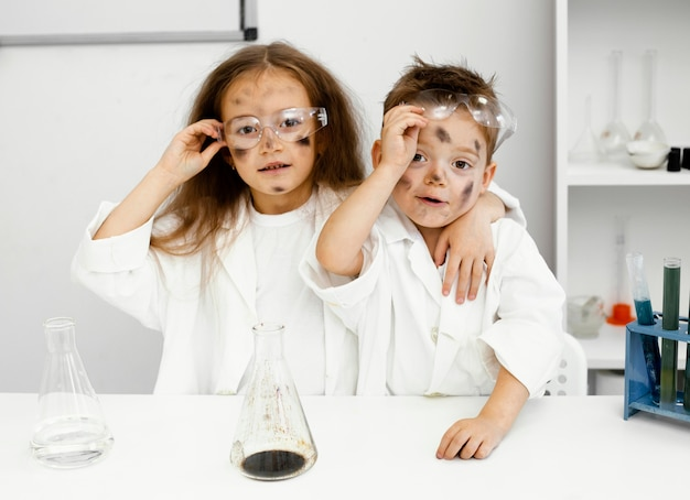 Süße mädchen- und jungenwissenschaftler im labor mit reagenzgläsern und fehlgeschlagenem experiment