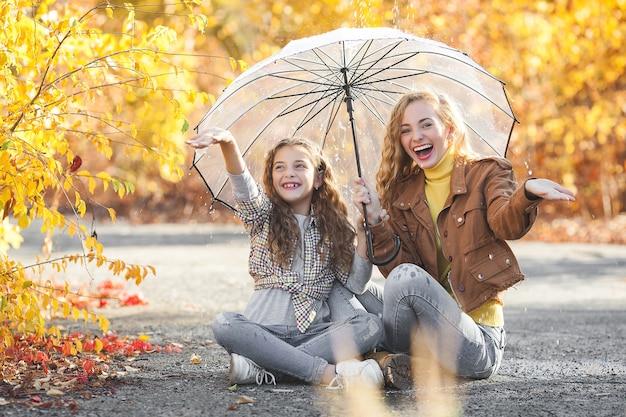 Süße mädchen unter regenschirm. freunde auf herbsthintergrund, der spaß hat.