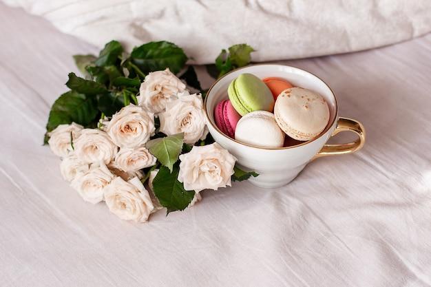 Süße makronen in becher und weißen rosen