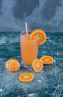 Süße mandarine und saft auf dem blauen hintergrund. hochwertiges foto