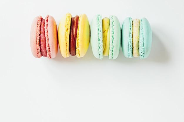 Süße mandel bunte pastellrosa blau gelb grün macaron oder makronen dessert kuchen isoliert auf weißem hintergrund. französischer süßer keks. minimales lebensmittelbäckereikonzept. flache draufsicht, kopienraum