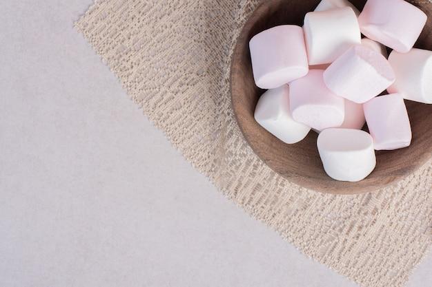 Süße marshmallows auf holzbrett auf sackleinen