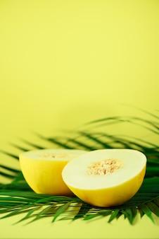 Süße melone über tropischen grünen palmblättern. pop-art-design, kreatives sommerkonzept. rohes veganes essen.
