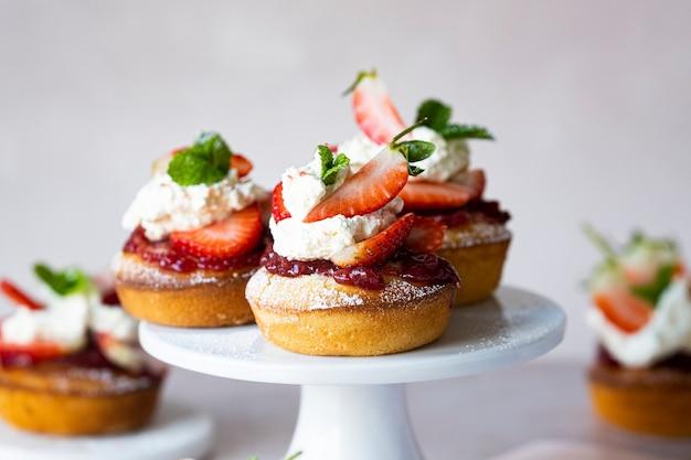 Süße mini-erdbeer-shortcakes auf einem ständer