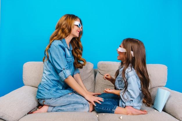 Süße momente der hübschen jungen mutter, die spaß mit tochter auf couch lokalisiert auf blauem hintergrund hat. modischer look in jeanskleidung, 3d-brille, der die positive einstellung der familie zum ausdruck bringt