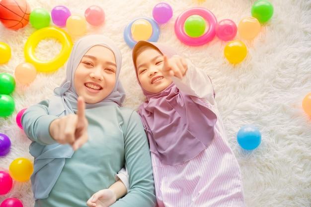 Süße muslimische arabische mutter und ihr mädchen spielen gerne zusammen mit bunten bällen, die spaß machen und schön sind