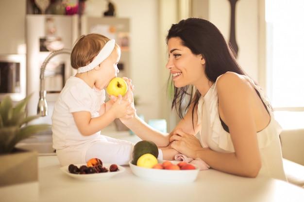 Süße mutter, die ihrem baby einen apfel gibt