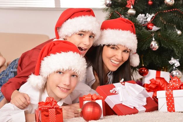 Süße mutter und ihre kinder in weihnachtsmützen mit geschenken