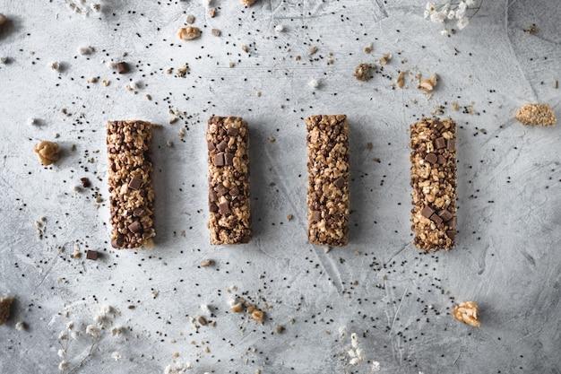 Süße natürliche fitnessriegel mit nüssen und getreide auf grauem hintergrund