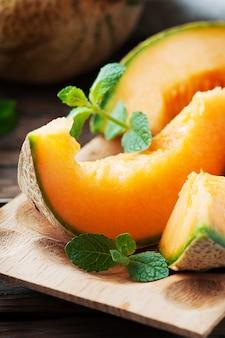 Süße orangenmelone auf dem holztisch