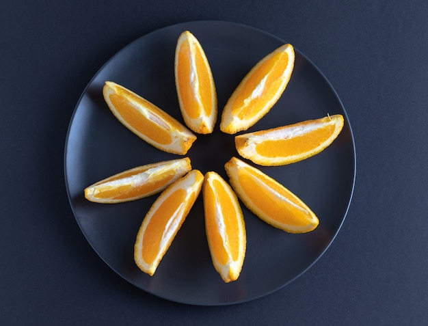 Süße orangenscheiben auf dunklem plat und dunklem hintergrund