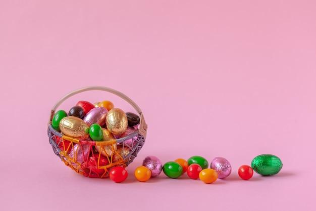 Süße ostersüßigkeitseier im korb auf rosa