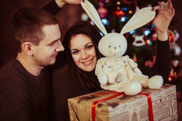 Süße paar hält weihnachtsschmuck und geschenk
