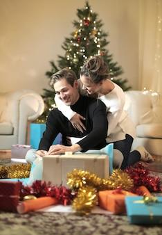 Süße paare, die ihren weihnachtsfeiertag, geschenke oben einwickelnd genießen