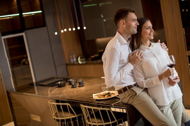 Süße paare, die trinkenden rotwein nach einem romantischen abendessen an der luxusküche essen