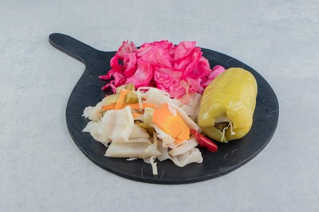 Süße paprika und sauerkraut auf dem schneidebrett auf der marmoroberfläche