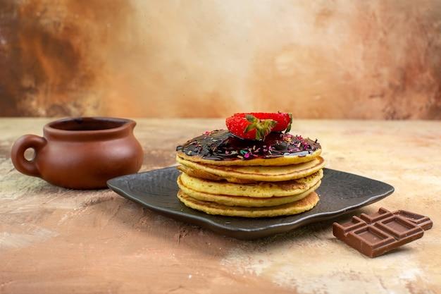 Süße pfannkuchen der vorderansicht mit schokoglasur auf hölzernem schreibtisch