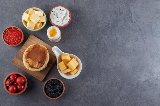 Süße pfannkuchen mit gekochtem ei und rotem frischem kirschtomatenhintergrund