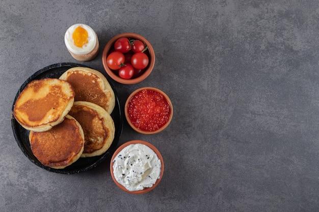 Süße pfannkuchen mit gekochtem ei und roten frischen kirschtomaten.